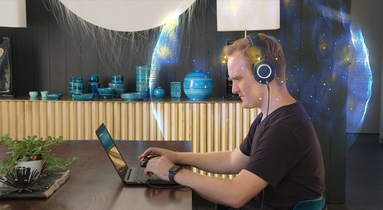 A man using headphones and a laptop with a bubble around his head